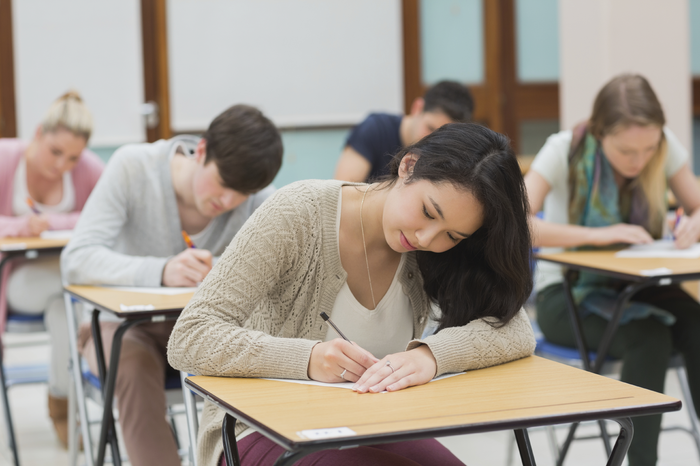 Students in a classroom sitting at their desks while doing a test